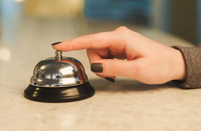 Woman ringing hotel reception service bell closeup